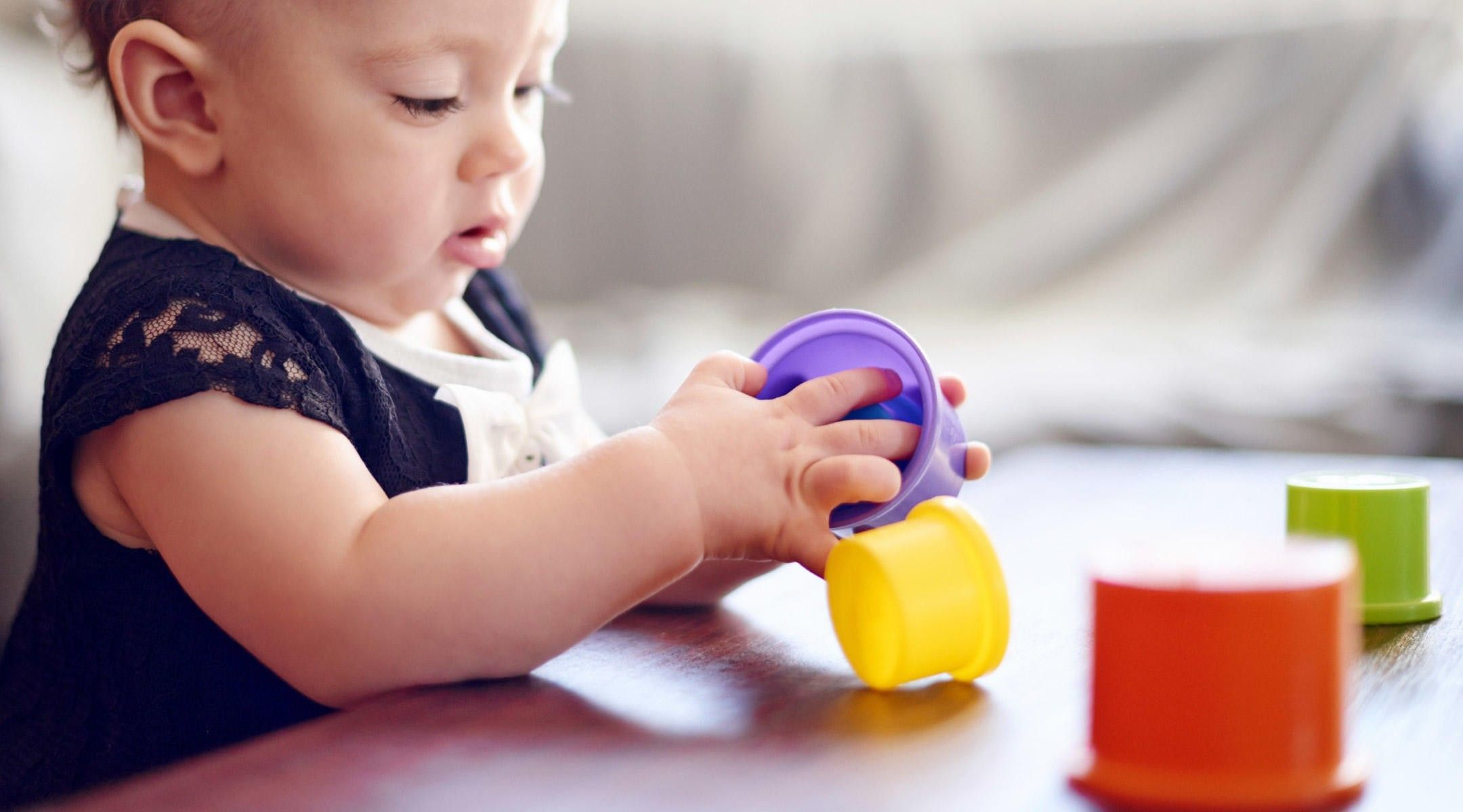 Baby playing with colourful cups